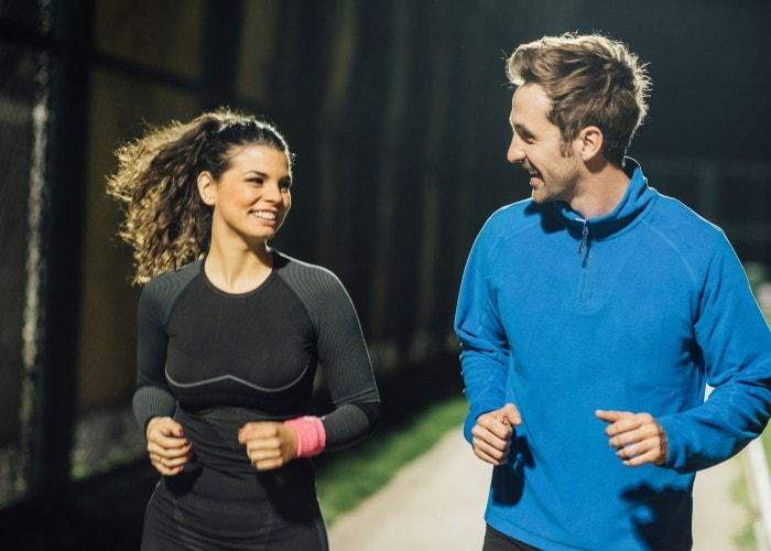 Par som jogger i godt opplyst park