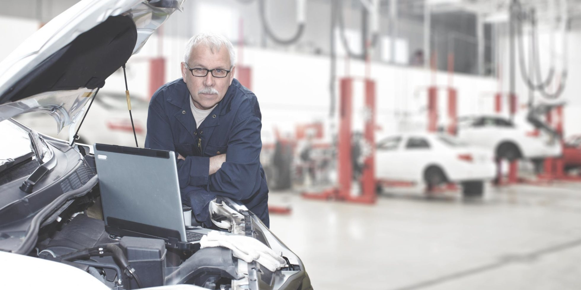 Bilmekaniker kjører diagnostikktest, bilverksted i bakgrunnen
