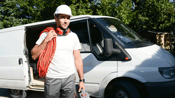 Electrical installer with a coiled cable around his shoulder