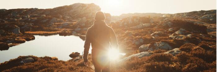 Mann går i lav høstsol på fjellet. Med len løsning for lading av elbil på hytta blir det lettere å ta turen.