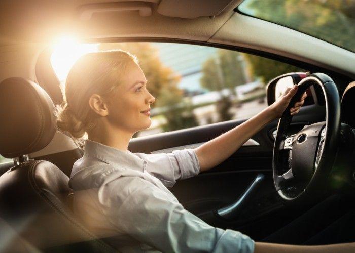 Smilende kvinne som kjører bil