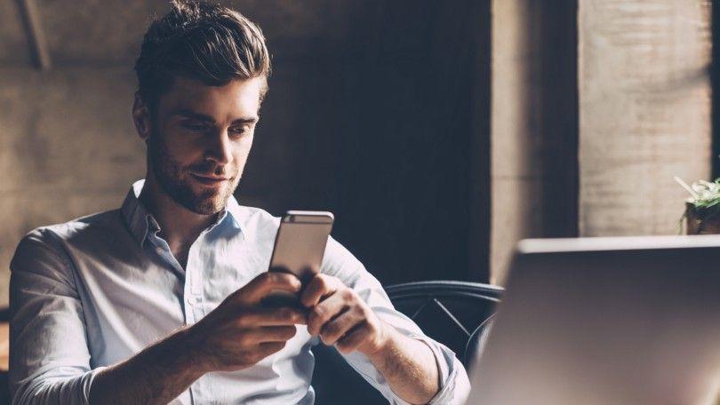 Mann som ser på mobiltelefon