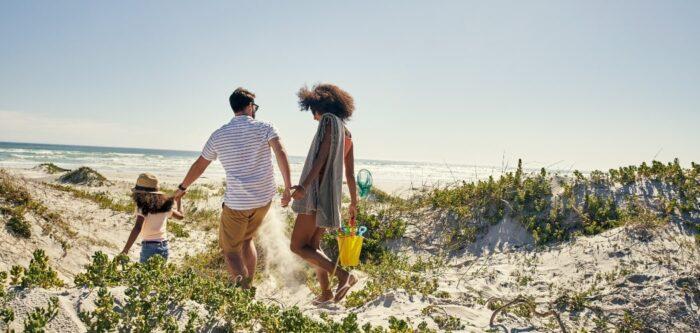 Leiende familie går på solfylt sandstrand