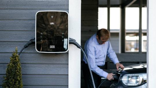 Ladestasjon montert på husvegg, med elbileier og elbil i bakgrunnen