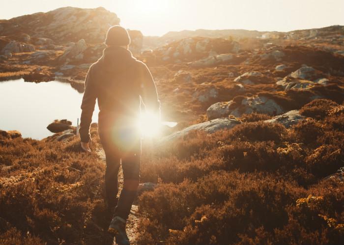 Mann i solnedgang ved fjellvann