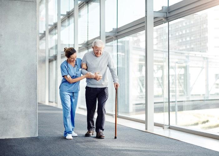 Lege støtter eldre mann mens han går i sykehuskorridor