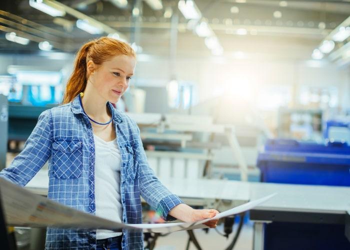 Kvinnelig medarbeider studerer arbeidstegninger