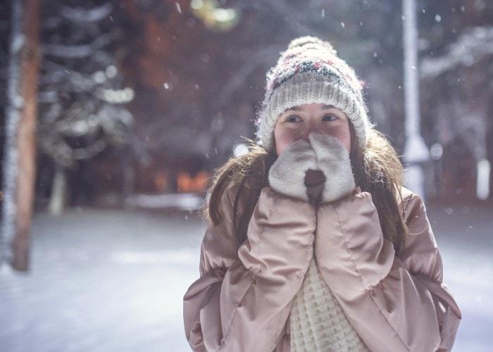 Jente som varmer hendene med pusten - park i vinterlandskap