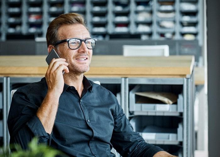 Mann snakker i mobiltelefon på kontor
