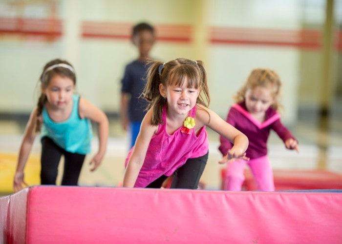 Girls running over mat in school gym