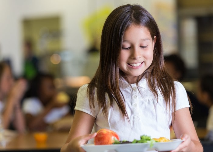 Girl with food in school cafeteria