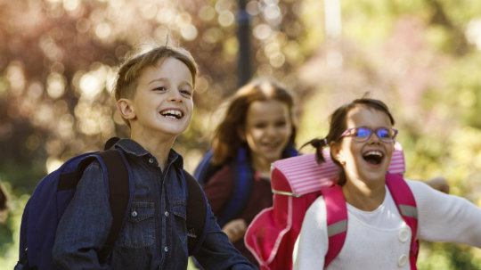 Happy school children running