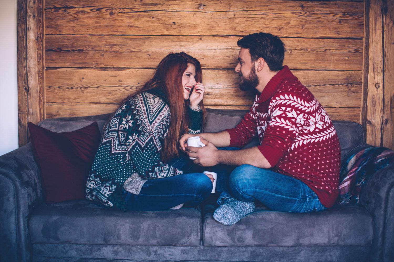 Et par hygger seg med ullgenser og te på en hytte